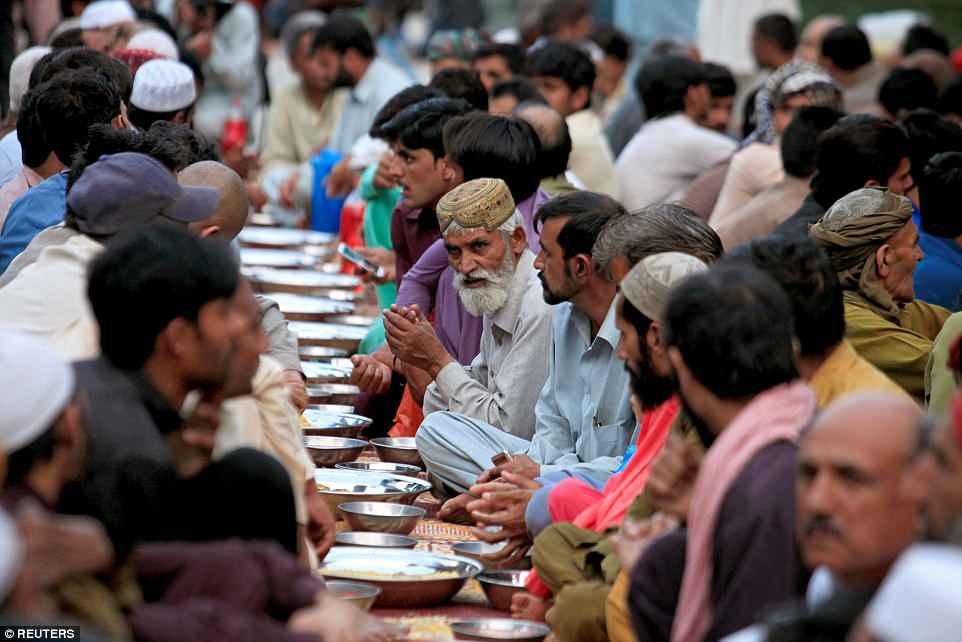Para pria berdoa sebelum berbuka puasa selama bulan suci Ramadhan di Rawalpindi, Pakistan